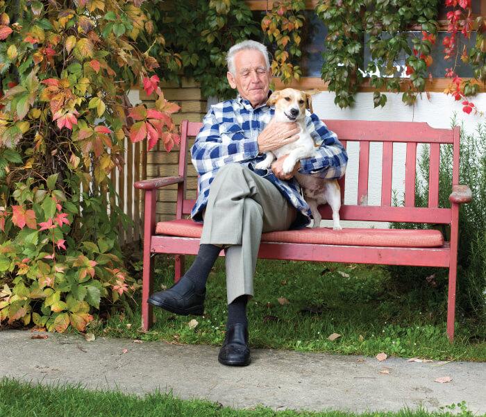 Image of man sitting patting dog