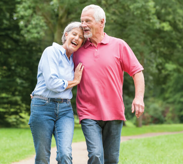 Image of man and women walking and laughing in the park