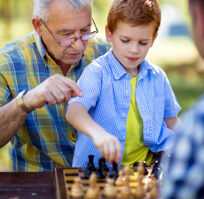 Image of a man teaching a child how to play chess