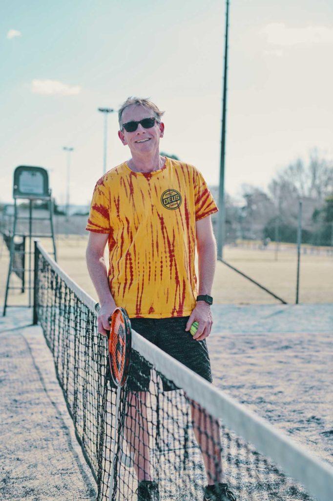 Man taking a break from tennis enjoying life