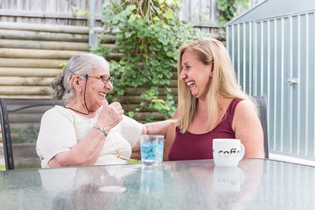 Mother and daughter sitting enjoy having coffee